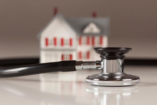 stethoscope in front of model house