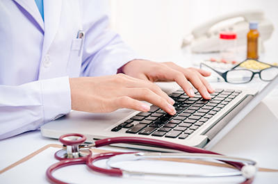 doctor hands typing on laptop
