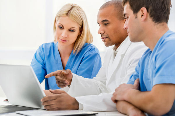 physician and staff checking laptop